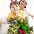 Father and son decorating a Christmas tree - Stock Photo