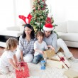 Happy family opening Christmas presents — ストック写真