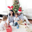 Happy family opening Christmas presents — Stock Photo