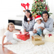 Family playing with Christmas gifts at home — Stock Photo #10294006