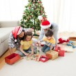 Happy family playing with Christmas presents at home — Stock Photo #10294015