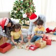 Family playing with Christmas presents at home — Stock Photo