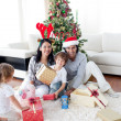 Family decorating a Christmas tree — Stock Photo #10294021