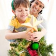 Father and son decorating a Christmas tree — Stock Photo