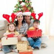 Family decorating a Christmas tree — Stockfoto