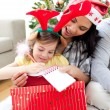 Mother and daughter playing with Christmas presents — Stock Photo