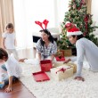 Family playing with Christmas gifts at home — Stock Photo