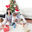Happy family opening Christmas presents — Stock Photo