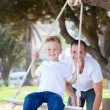 Stock Photo: Jolly father pushing his son on a swing