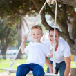 Jolly father pushing his son on a swing — Stock Photo