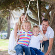 Happy parents pushing their children on a swing — Stock Photo