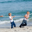 Happy family playing tug of war — Stock Photo