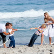 Stock Photo: Cheerful family playing tug of war