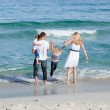 Jolly family walking on the sand — Stockfoto #10294079