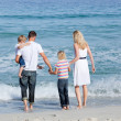 Happy family walking on the sand — Stock Photo #10294081