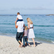 Affectionate family walking on the sand — Stock Photo #10294083