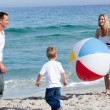 Stock Photo: Happy parents and their son playing with ball