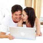 Enamoured couple using laptop — Stock Photo