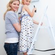 Mother and her little girl painting a room — Stock Photo