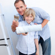 Smiling father and his son holding paintbrush — Stock Photo #10294237