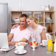 Happy couple using a laptop while having breakfast — Stock Photo