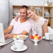 Stock Photo: Enamored couple using laptop while having breakfast