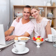 Affectionate couple using a laptop while having breakfast — Stock Photo