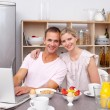 Young couple using a laptop while having breakfast — Stock Photo