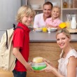 Attentive mother packing the school lunch to his son — Stock Photo