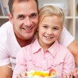 Happy little girl eating fruit with her father — Stock Photo