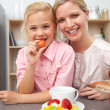 Attentive mother eating fruit with her daughter — Stock Photo