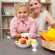 Stock Photo: Caring mother eating fruit with her daughter