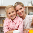 Jolly little girl eating fruit with her mother — Stock Photo