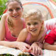 Stock Photo: Carring mother and her little girl lying on grass