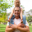 Happy father giving his daughter piggy-back ride — Stock Photo