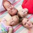 Jolly family sleeping lying on the grass — Stock Photo #10294333