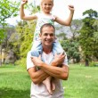 Stock Photo: Jolly father giving his daughter piggy-back ride