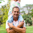 Joyful father giving his daughter piggy-back ride — Stockfoto