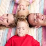 Cheerful family sleeping lying on the grass — Stock Photo