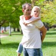 Joyful father giving his daughter piggy-back ride — Stock Photo