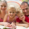 Portrait of a happy family lying on the grass — Stock Photo