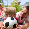 Father and son holding a soccer ball with their family reading i — Stock Photo