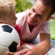 Close-up of an attentive father and his son holding a soccer bal — Stock Photo