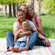 Stock Photo: Portrait of young family having a picnic