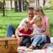 Young family relaxing while having a picnic — Stock Photo