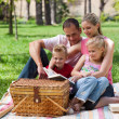 Smiling family reading while having a picnic — Stock Photo