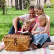 Happy family reading in a park — Stockfoto