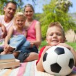 Little boy having fun with a soccer ball with his family smiling — Stock Photo