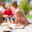 Serious little girl reading while having a picnic — Stock Photo