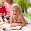 Close-up of a little girl reading at a picnic — ストック写真